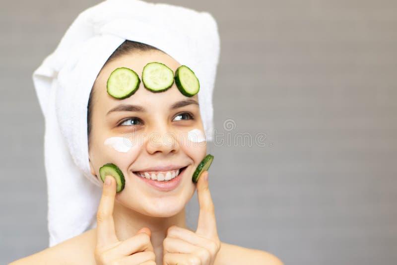 Młoda piękna dziewczyna z ogórków plasterkami na twarzy nad białym tłem Piękno kosmetologia i skincare fotografia royalty free