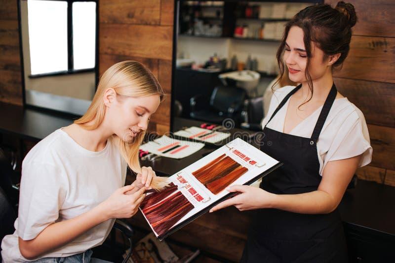 Młoda piękna kobieta i fryzjer porównuje jej blondynka włosy z koloru włosy od palety przed poprawną kolorystyką obraz stock