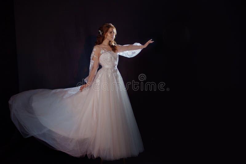 Młoda piękna kobieta w ślubnej sukni z szeroką światło spódnicą Ciemny tło, fantazja styl fotografia royalty free