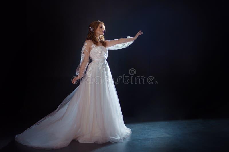 Młoda piękna kobieta w ślubnej sukni z szeroką światło spódnicą Ciemny tło, fantazja styl obraz royalty free