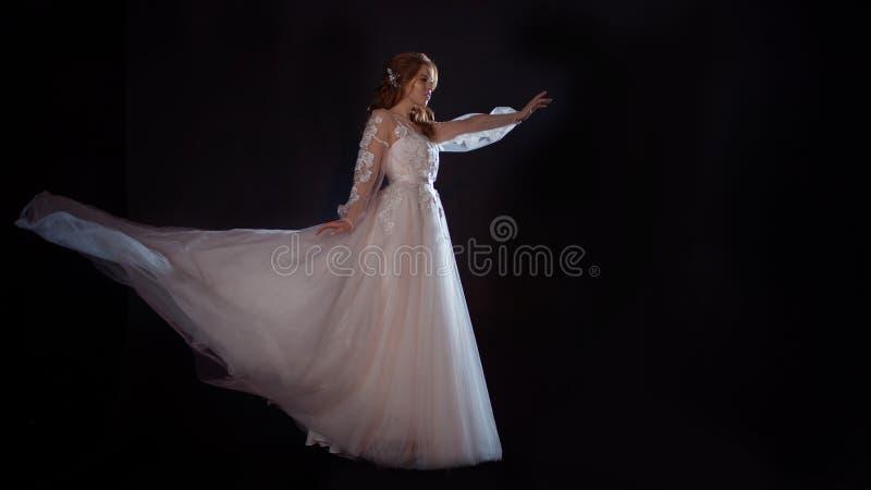 Młoda piękna kobieta w ślubnej sukni z szeroką światło spódnicą Ciemny tło, fantazja styl fotografia stock