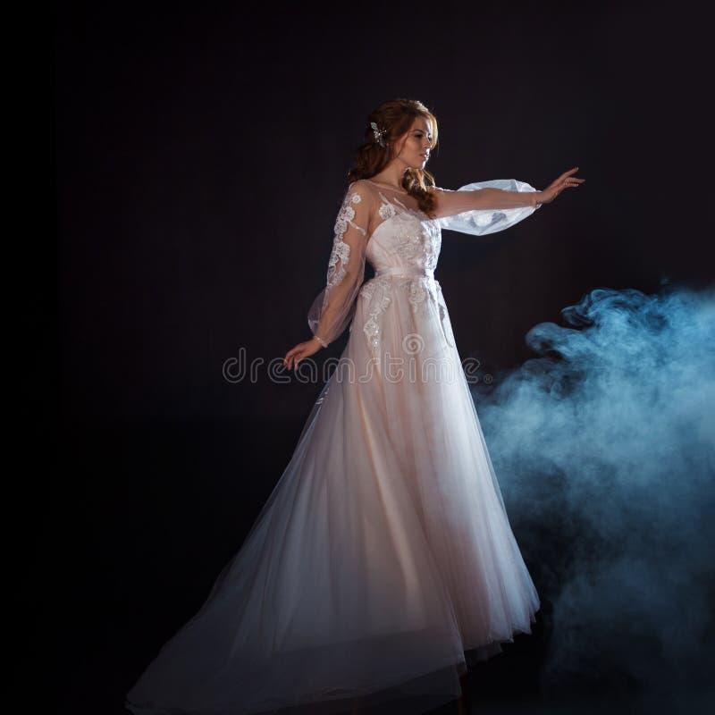 Młoda piękna kobieta w ślubnej sukni z szeroką światło spódnicą Ciemny tło, fantazja styl zdjęcia stock