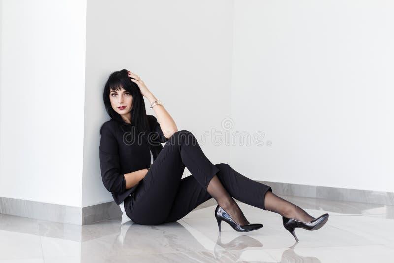 Młoda Piękna poważna brunetki kobieta ubierał w czarnym garnituru obsiadaniu na podłodze w biurze obrazy royalty free