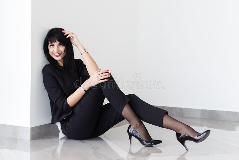 Młoda Piękna szczęśliwa brunetki kobieta ubierał w czarnym garnituru obsiadaniu na podłodze patrzeje kamerę w biurze, ono uśmiech zdjęcie stock