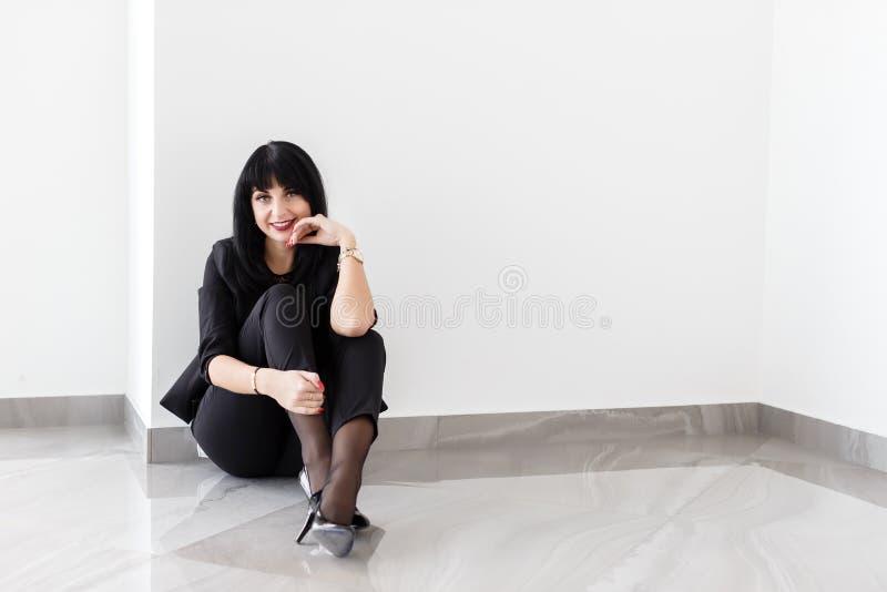 Młoda Piękna szczęśliwa brunetki kobieta ubierał w czarnym garnituru obsiadaniu na podłodze patrzeje kamerę w biurze, ono uśmiech zdjęcia royalty free