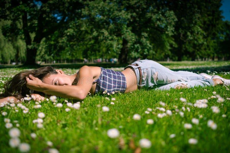 Młoda radosna kobieta kłama na zielonej trawie obrazy royalty free