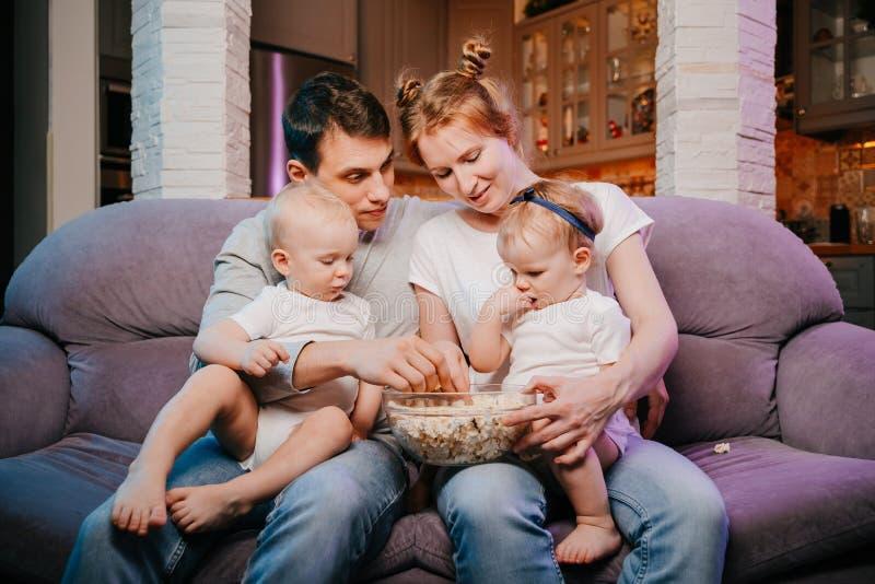 Młoda rodzina z dziećmi je popkorn na leżance zdjęcia royalty free