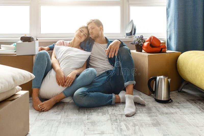 Młoda rodzinna para kupował ich pierwszy małego mieszkanie lub dzierżawił Ludzie siedzą na podłodze i śpią Zmęczony i skołowany fotografia stock