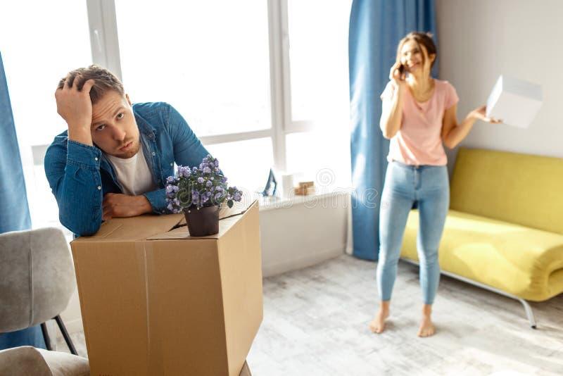 Młoda rodzinna para kupował ich pierwszy małego mieszkanie lub dzierżawił Zmęczony zanudzający mężczyzna patrzeje skołowanym Młod obraz stock