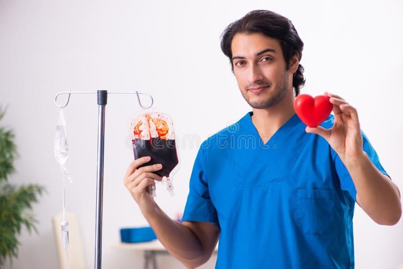 Młoda samiec lekarka w krwionośnego przetaczania pojęciu zdjęcie stock