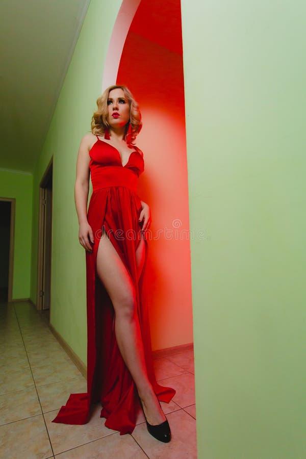 Młoda seksowna blondynki kobieta w czerwonej sukni z wysokości rozchyleniem obrazy royalty free