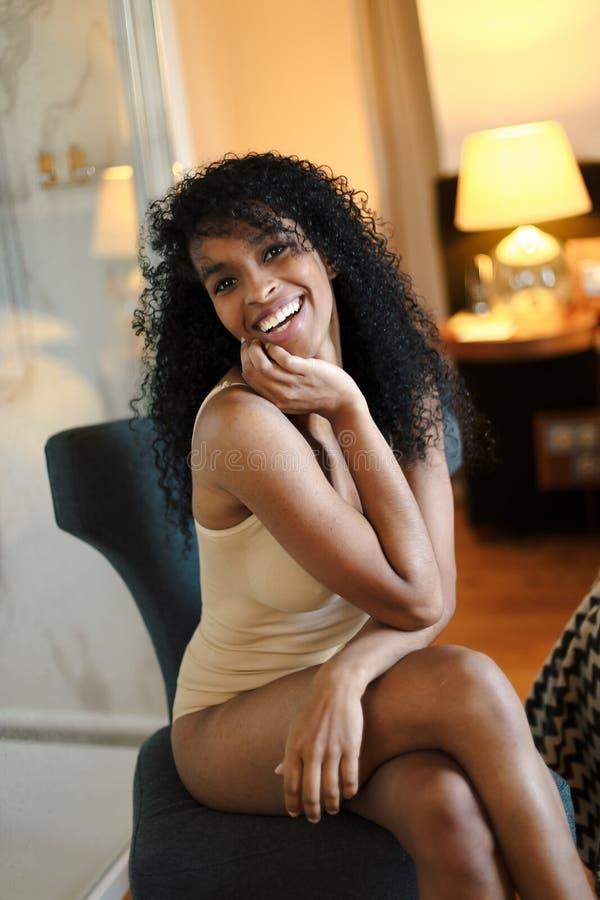 Młoda szczęśliwa afro amerykańska dziewczyna jest ubranym bieliznę i obsiadanie w sypialni zdjęcie stock