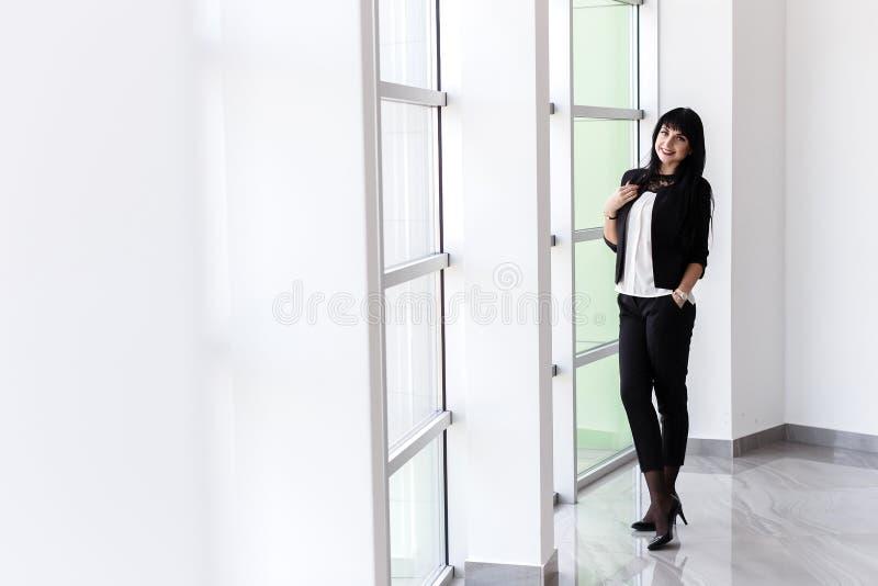 Młoda szczęśliwa brunetki kobieta patrzeje kamerę ubierał w czarnej garnitur pozycji blisko okno w biurze, ono uśmiecha się, zdjęcie royalty free