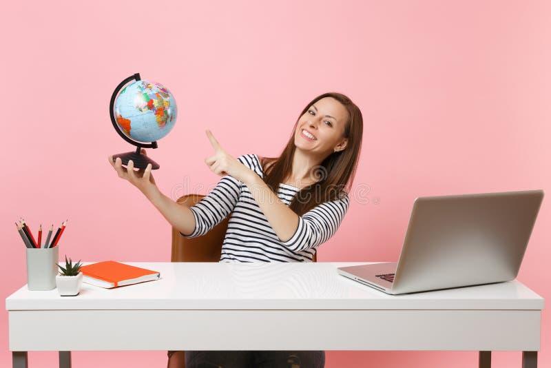 Młoda szczęśliwa kobieta wskazuje na kuli ziemskiej, planuje wakacje, pracuje przy biurem przy białym biurkiem z współczesnym kom obrazy stock