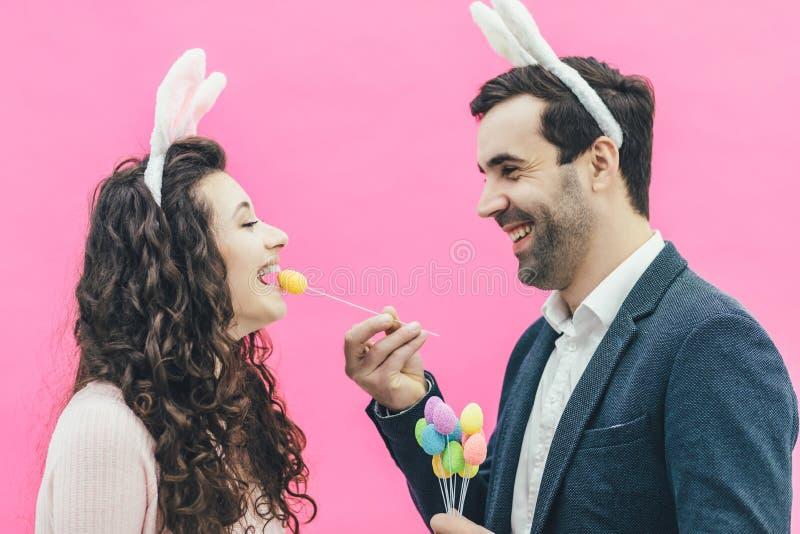 Młoda szczęśliwa rodzina na różowym tle W tym samym czasie na głowie są królika ucho tam Podczas ten mężczyzny mienia obrazy stock