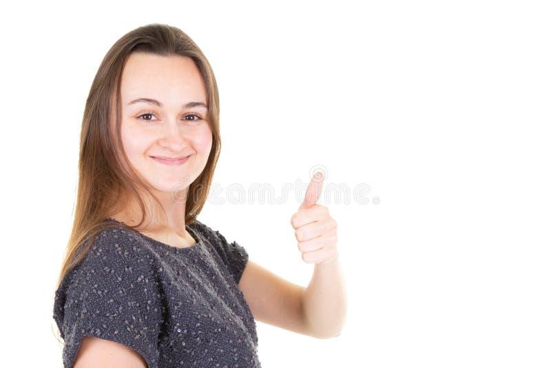 Młoda szczęśliwa rozochocona kobieta pokazuje kciuk w górę dawać aprobatom przeciw białemu tła miejscu dla teksta zdjęcia royalty free