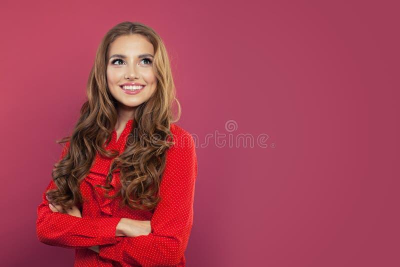Młoda szczęśliwa uśmiechnięta kobieta przyglądająca w górę jaskrawych kolorowych menchii przeciw izoluje tło Portret śliczna dosy fotografia stock