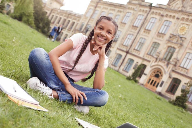 Młoda uczennica przy szkolnego jarda obsiadaniem na gazonie z notatnikami i laptopem robi pracy domowej przyglądającej kamerze fi obraz royalty free
