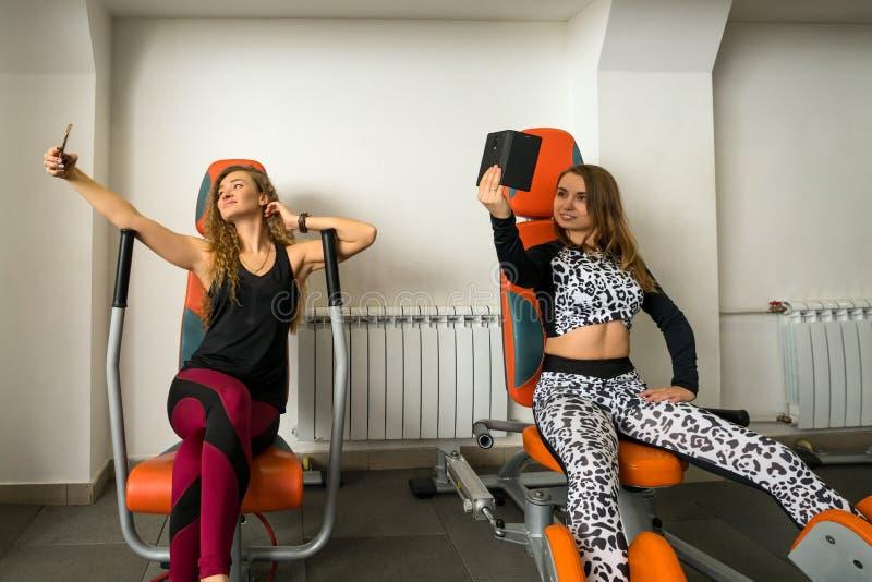 Młode kobiety na stażowym aparacie w gym strzale fotografia stock