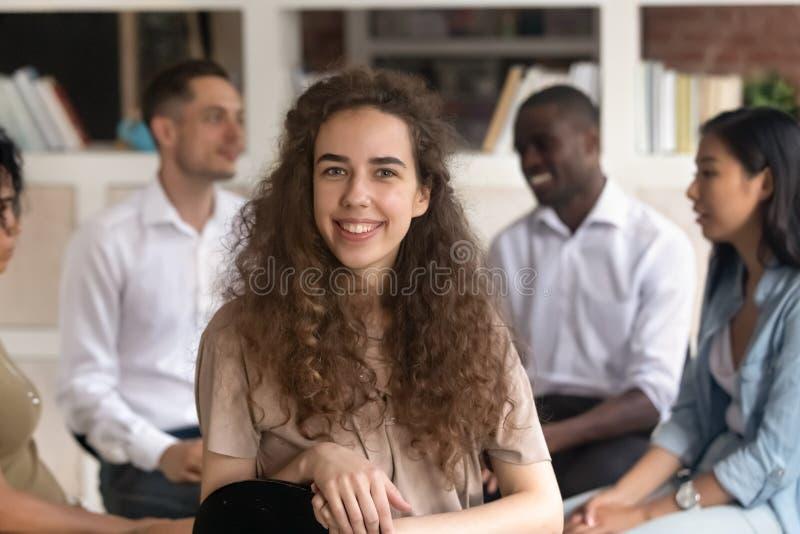 Młodego żeńskiego terapeuty stażowego uczestnika powozowy pozować przy grupową terapią obrazy stock