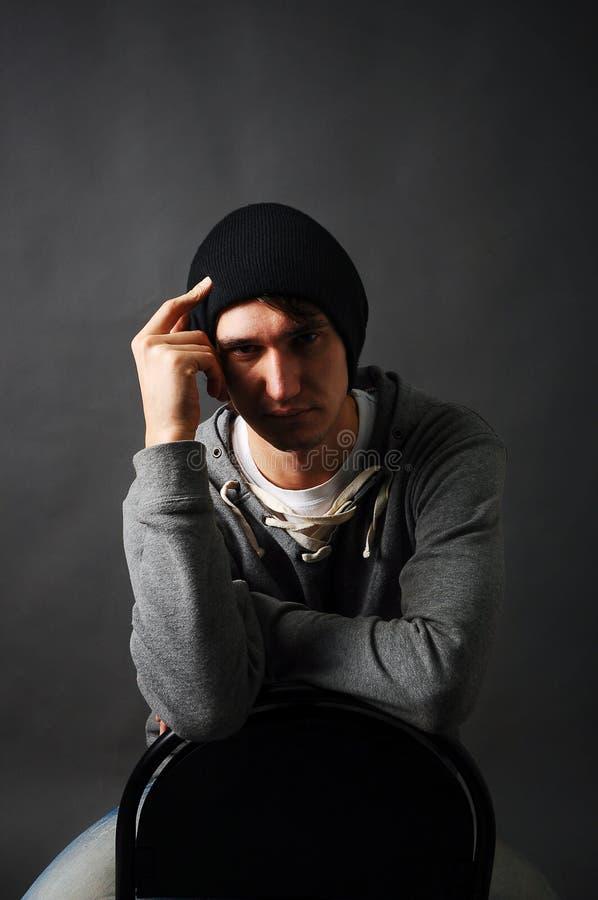 Młodego człowieka obsiadanie na krześle trzyma jego rękę jego głowa w cieniu w szarym hoodie i czarnym kapeluszu zdjęcia stock