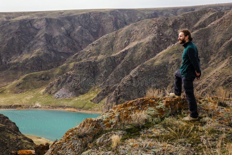 Młodego człowieka stojaki na krawędzi falezy i spojrzenia przy doliną z rzeką duże krajobrazowe halne góry Wiosna Ili rzeka obraz stock