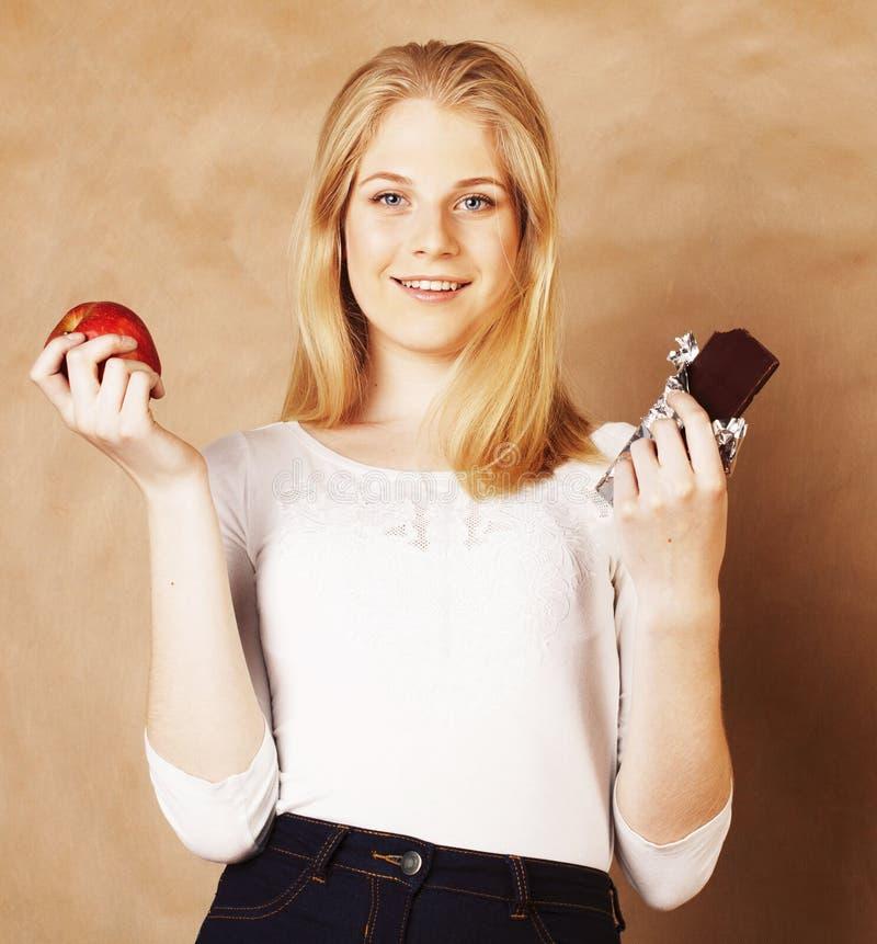Młodego piękno nastoletniej dziewczyny blond łasowania czekoladowy ono uśmiecha się, wybór między cukierki i jabłko, zdjęcie stock
