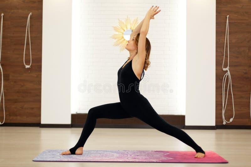 Młodej kobiety ćwiczy joga w jaskrawym gym Streching i wellness styl życia fotografia stock
