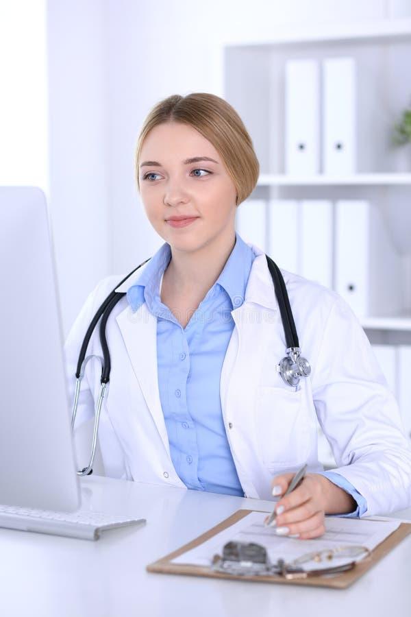 Młodej kobiety lekarka przy pracą w szpitalnym patrzeje komputeru stacjonarnego monitorze Lekarz kontroluje lekarstwo historii re obrazy royalty free