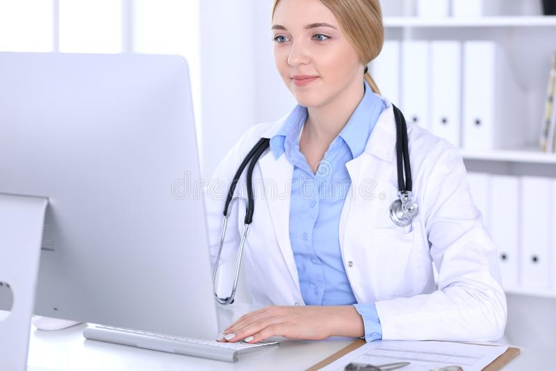Młodej kobiety lekarka przy pracą w szpitalnym patrzeje komputeru stacjonarnego monitorze Lekarz kontroluje lekarstwo historii re fotografia royalty free