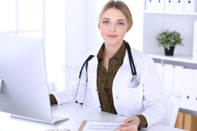 Młodej kobiety lekarka przy pracą w szpitalnym patrzeje komputeru stacjonarnego monitorze Lekarz kontroluje lekarstwo historii re zdjęcia royalty free