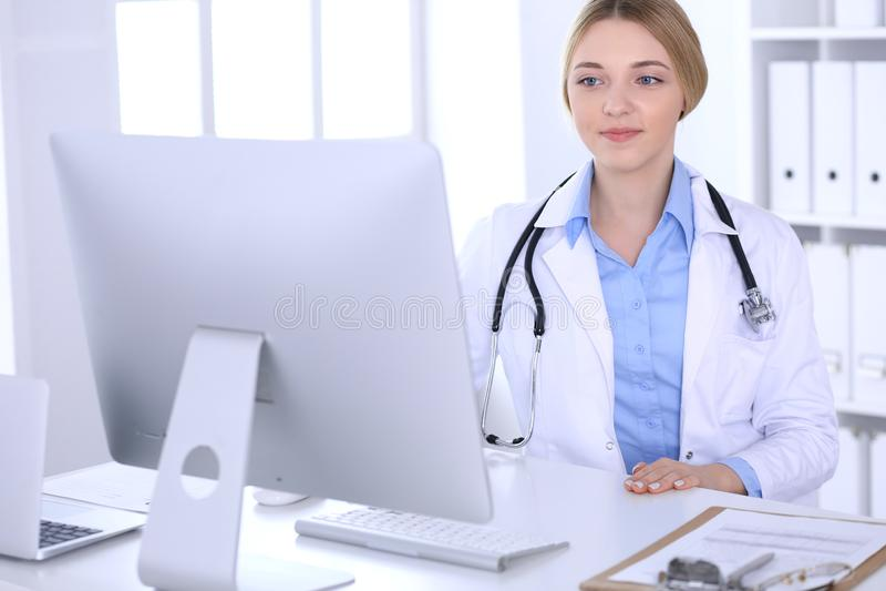 Młodej kobiety lekarka przy pracą w szpitalnym patrzeje komputeru stacjonarnego monitorze Lekarz kontroluje lekarstwo historii re zdjęcia stock