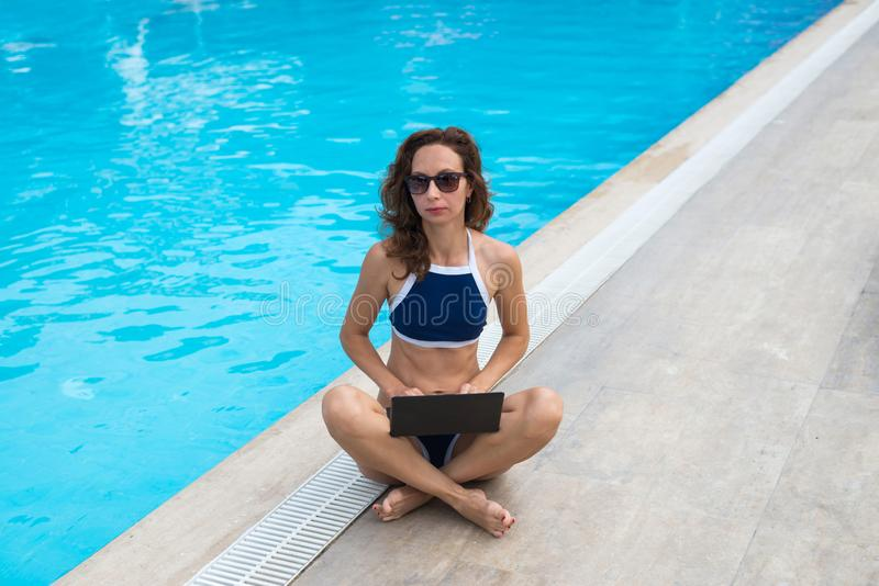 Młodej kobiety obsiadanie basenem i działanie na laptopie Kobiety workaholic działanie podczas gdy na urlopowej, bezpłatnej przes zdjęcia stock