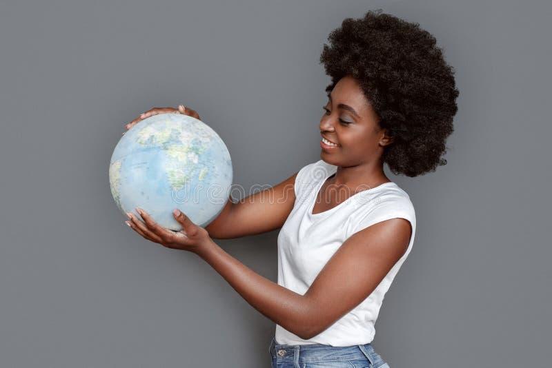 Młodej kobiety pozycja odizolowywająca na szary patrzeje kuli ziemskiej miejsce przeznaczenia podróżny ono uśmiecha się rozochoco obrazy stock