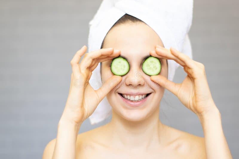 Młodej pięknej dziewczyny uśmiechnięty chować ono przygląda się za ogórkowymi plasterkami nad białym tłem Piękno kosmetologia i s fotografia stock
