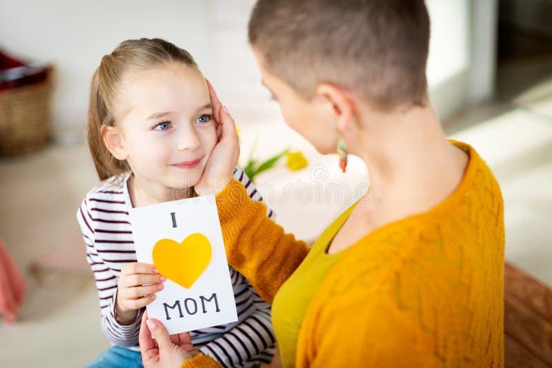 Młody żeński pacjent z nowotworem dziękuje jej uroczej młodej córki dla domowej roboty KOCHAM mamy kartkę z pozdrowieniami szczęś fotografia stock