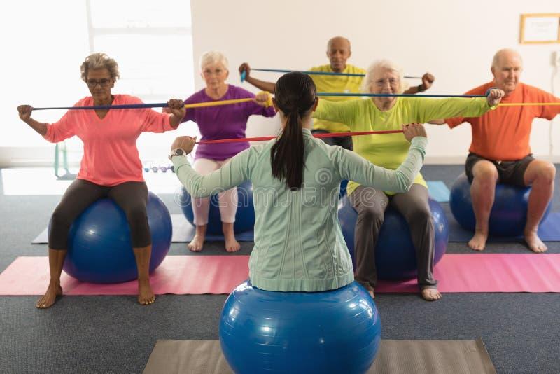 Młody żeński trener i starszy ludzie ćwiczy z oporem skrzykniemy zdjęcie royalty free