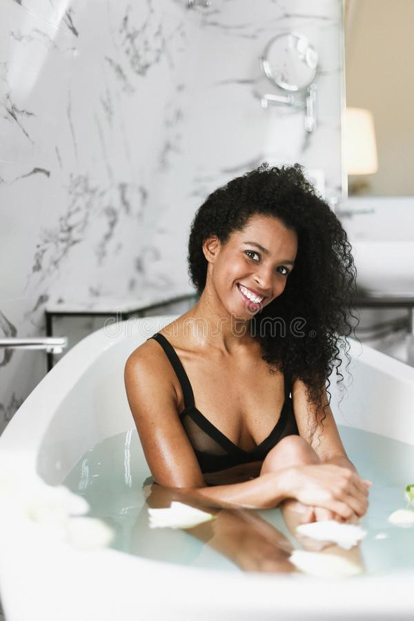 Młody ładny afro amerykański dziewczyny obsiadanie w skąpaniu, jest ubranym czarnego swimsuit obraz royalty free