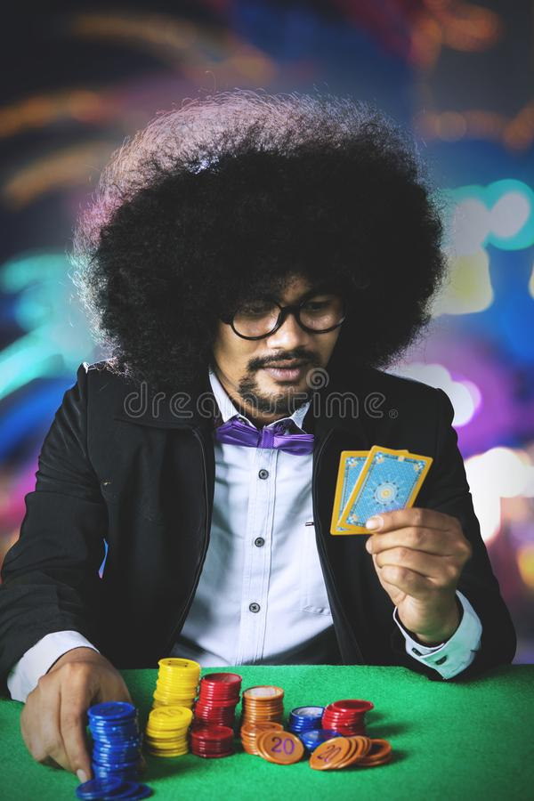 Młody Afro mężczyzna trzyma grzebak karty w kasynie obraz royalty free