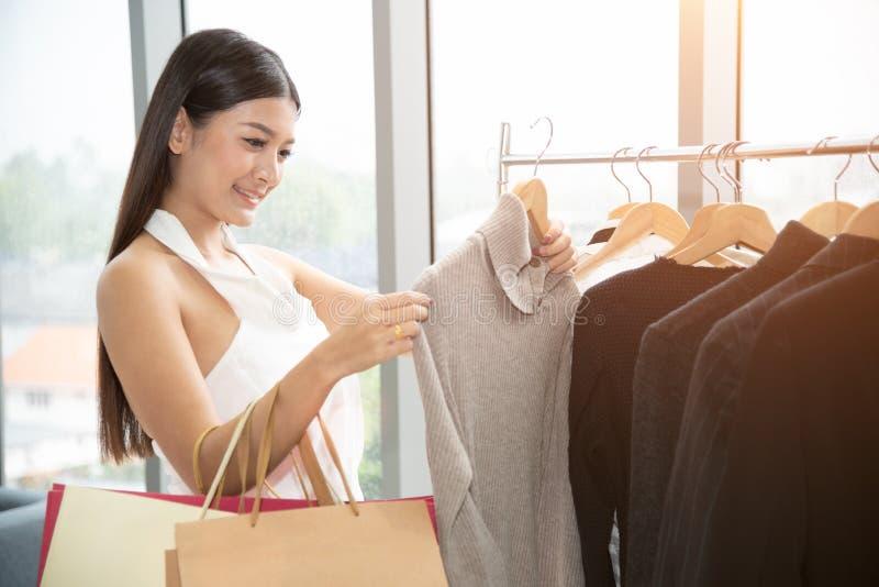 Młody atrakcyjny azjatykci kobiety robić zakupy modny odziewa w centrum handlowym fotografia stock