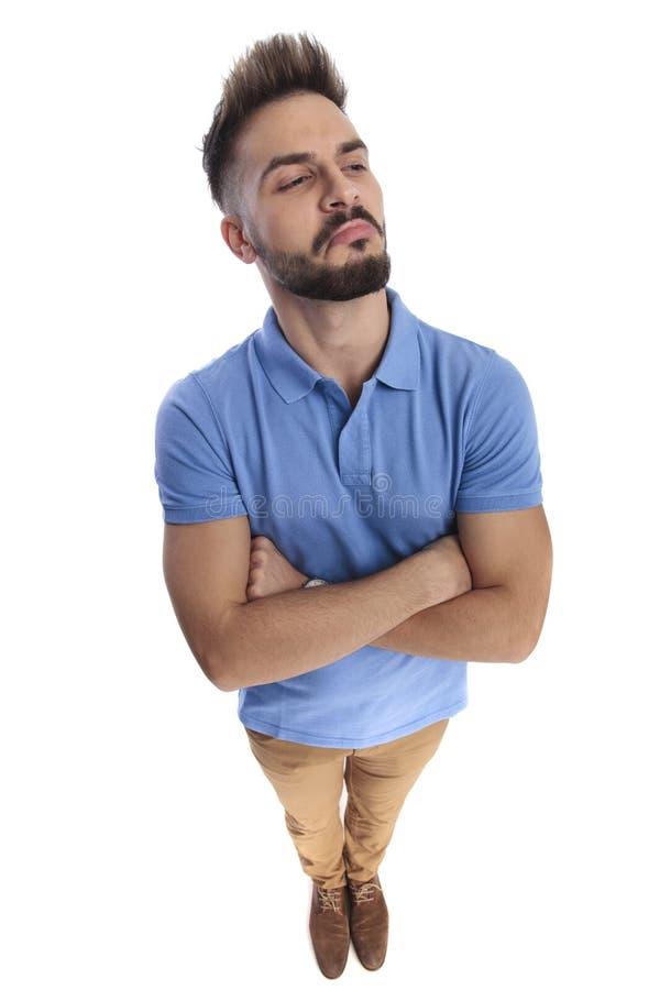 Młody atrakcyjny mężczyzna jest ubranym bławego polo patrzeje stronę zdjęcia royalty free