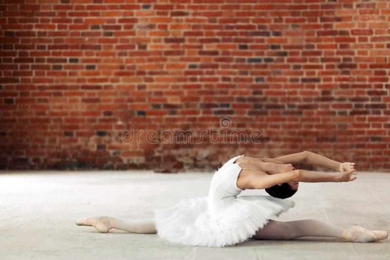 Młody baletniczy tancerz zgina ona z powrotem podczas gdy wykonywać rozszczepia fotografia stock