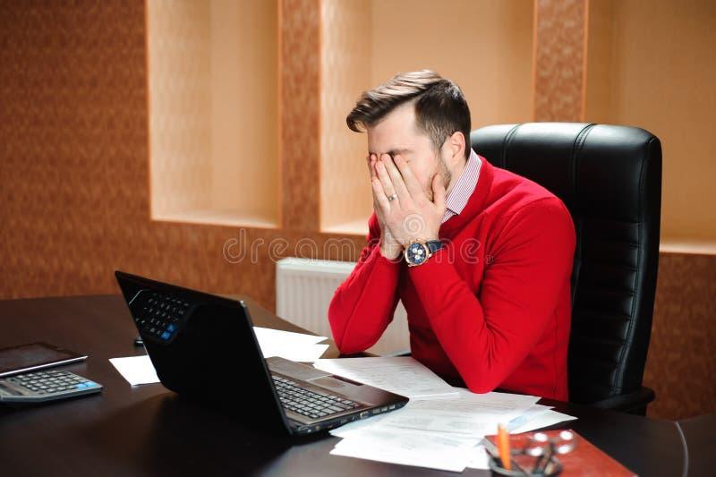Młody biznesmen marszczy brwi przy jego ekranem komputerowym z problemem przy biurowym obsiadaniem przy jego biurkiem obraz stock