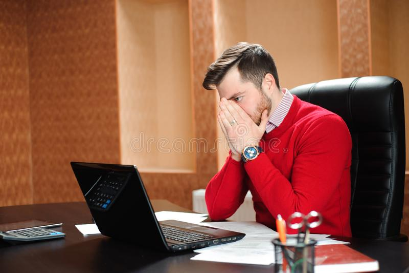 Młody biznesmen marszczy brwi przy jego ekranem komputerowym z problemem przy biurowym obsiadaniem przy jego biurkiem fotografia royalty free