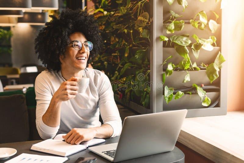 Młody biznesmen z kawowym działaniem na laptopie w kawiarni obraz royalty free