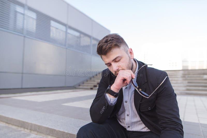 Młody biznesowego mężczyzny płacz porzucający gubjącym w depresji obsiadaniu na zmielonych ulica betonu schodkach zdjęcia stock
