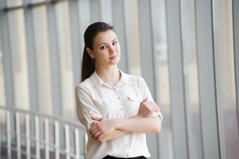Młody bizneswoman opowiada na telefonie komórkowym podczas gdy stojący okno w biurze Piękny młody kobieta model w biurze zdjęcie stock