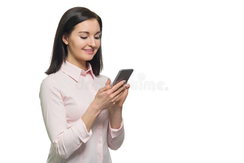 Młody bizneswoman w różowym koszulowym używa telefonie komórkowym na białym odosobnionym tle Kobieta pisze wiadomości tekstowej l zdjęcia royalty free