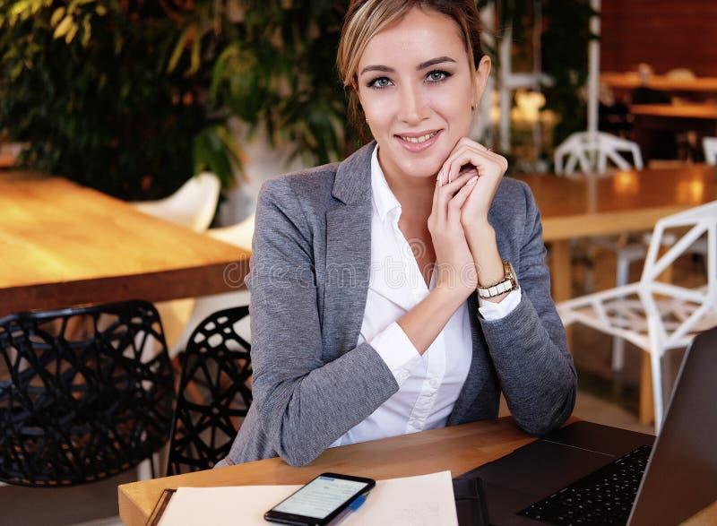 Młody bizneswomanu obsiadanie przy biurkiem i działaniem Uśmiechnięty i patrzejący kamerę Styl życia, ludzie i biznesowy pojęcie, zdjęcia royalty free