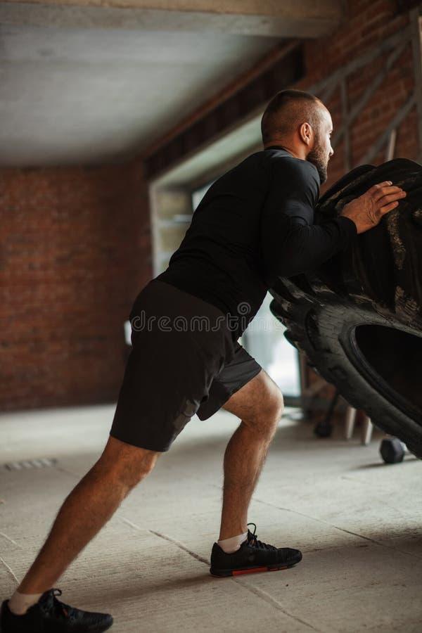 Młody caucasian mięśniowy mężczyzna podrzuca ciężką oponę w gym obraz stock